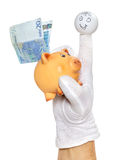 Finger puppet holding piggybank with euro note. Happy finger puppet holding twenty euro note on piggy bank back Stock Image