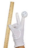Finger puppet holding wooden rule Royalty Free Stock Photography