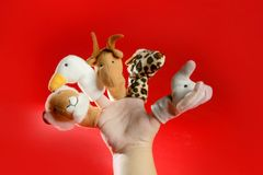 Finger puppets on a toddler hand over red Stock Photo