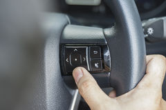 The Finger Push a button on the car steering wheel Stock Image