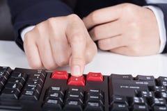 Finger pushing arrow button on keyboard computer stock photos