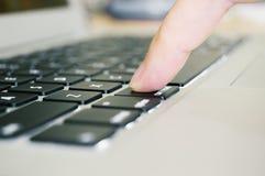 Finger pushing button on laptop keyboard stock photography
