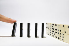 Finger pushing domino Stock Photos