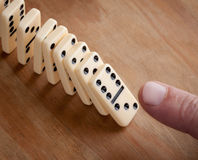 Finger pushing domino pieces Royalty Free Stock Photos
