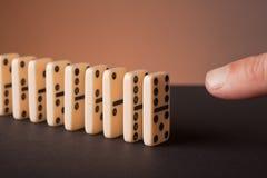 Finger pushing dominoes Royalty Free Stock Image