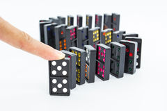 Finger pushing dominoes. Royalty Free Stock Photos