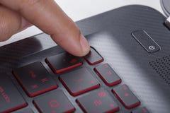 Finger pushing esc button on laptop keyboard Stock Image