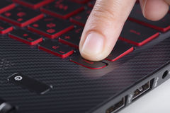 Finger pushing esc button on laptop keyboard Stock Photo