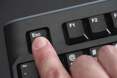 Finger pushing Esc key on black keyboard Royalty Free Stock Photo