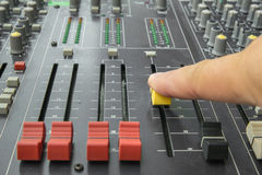 Finger pushing a mixing desk slide. Selective focus Stock Photography