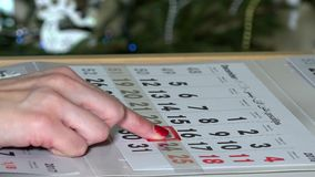 Finger pushing paper calendar marker till Christmas holiday