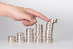 Finger pushing a pile of coins, column of coins falls , business Stock Photos
