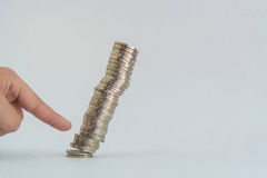 Finger pushing a pile of coins, column of coins falls , business Stock Image