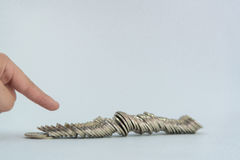 Finger pushing a pile of coins, column of coins falls , business Royalty Free Stock Image
