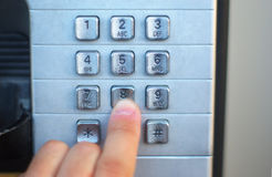 Finger pushing telephone button public cabin, metallic buttons. Dialing on public telephone touch pad height number Stock Photos