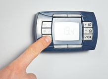 Finger pushing thermostat control button Royalty Free Stock Image