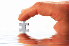 Finger and puzzle in water. On white Royalty Free Stock Image