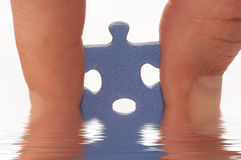 Finger and puzzle in water. On white Stock Images