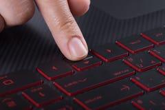 Finger que empuja el botón de la flecha en el teclado del ordenador portátil Fotografía de archivo