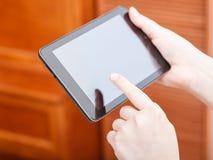 Finger que hace clic la PC de la tableta en oficina Fotografía de archivo