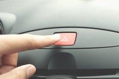Finger que presiona el botón de la emergencia del coche imagenes de archivo