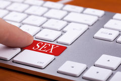Finger que presiona en el botón rojo con palabra del sexo en ella Fotos de archivo libres de regalías