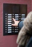 Finger que presiona la campana de puerta en la construcción de viviendas Imagen de archivo libre de regalías