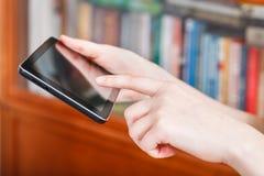Finger que presiona la PC de la tableta en biblioteca Foto de archivo