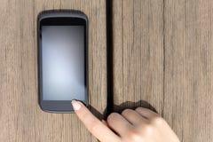 Finger que presiona una pantalla táctil elegante en blanco del teléfono Fotos de archivo libres de regalías