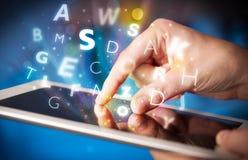 Finger que señala en la PC de la tableta, concepto de las letras Foto de archivo