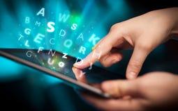 Finger que señala en la PC de la tableta, concepto de las letras Imagen de archivo libre de regalías