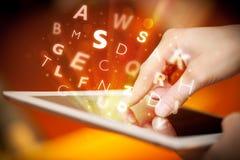 Finger que señala en la PC de la tableta, concepto de las letras Imágenes de archivo libres de regalías