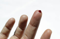 A finger with red blood drop. On a white background Stock Photos