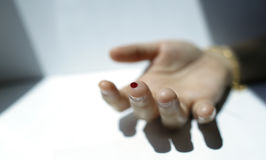 A finger with red blood drop Royalty Free Stock Photos