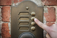 Finger ringing a door bell. A visitor pushing a brass, antique doorbell mounted to a brick wall royalty free stock photo