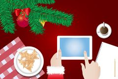 Finger of Santa Claus is touching a blank screen of tablet. Ready for your text over the table with  branch of Christmas tree, Christmas sweets on the plate and Stock Photos