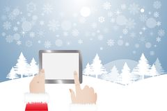 Finger of Santa Claus touching tablet in winter landscape. View of finger of Santa Claus touching tablet with blank screen ready for your text. Winter snowy Royalty Free Stock Images