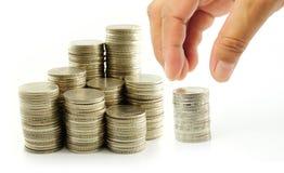 Finger satt mynt på mynt-bunt Arkivbild