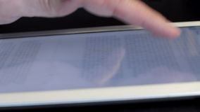 Finger scrolling text screen on tablet. Finger man scrolling text screen on tablet. Close up stock video