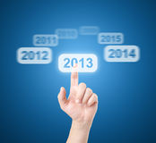 Finger selects touchscreen 2013. On blue background Stock Image