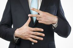 Finger seven. Breast and ventral view of a young man in a black suit with hands held out showing the 7 (seven finger Stock Photo