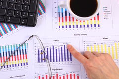 Finger showing financial graph, glasses, computer keyboard and cup of coffee, business concept Royalty Free Stock Photos