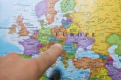 Finger som pekar till en färgrik landsöversikt av Europa som avgör vilket land för att semestra och resa fotografering för bildbyråer