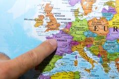 Finger som pekar till en färgrik landsöversikt av Paris, Frankrike i Europa arkivbild