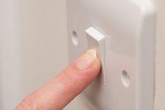 Finger som trycker på PÅ den ljusa strömbrytaren på väggKOPIERINGSUTRYMME Fotografering för Bildbyråer