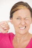 Finger subrayado preocupante de la mujer en oído fotos de archivo
