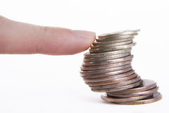 Finger supporting the column of coins. On the white background Royalty Free Stock Image