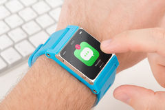 Finger taps messenger icon on blue smart watch Royalty Free Stock Image