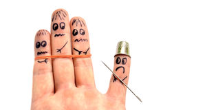 Finger in thimble armed by needle puts in fear another fingers Stock Image