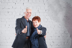 Finger to the top, like. Happy smiling old couple standing cuddling together isolated on white brick background. copy Royalty Free Stock Images
